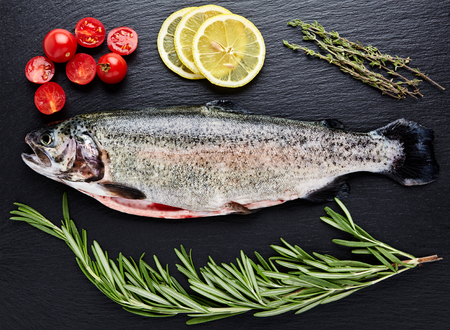 gutted: Close up shot of raw fresh rainbow trout on a black background with halved cherry tomatoes, slices of lemon and sprigs of rosemary. Preparations for cooking delicious fish. Stock Photo