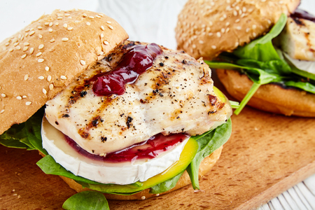 strawberry jam sandwich: Homemade grill chicken burger or sandwich with mango, Camembert cheese, cranberry sauce, fresh spinach and toasted buns. The perfect lunch on cutting board. Bowl of jam near White, wood background
