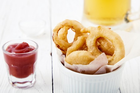 flavorful: Close up shot of delicious, crunchy, golden onion rings in a white bowl with a paper, a ketchup shot next to it on wooden table. Appetizing flavorful snack for beer. Fastfood from the deep fryer. Stock Photo