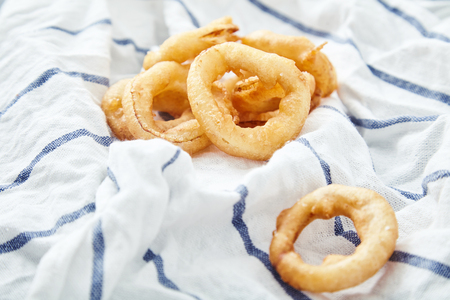flavorful: Close up shot of delicious, crunchy, golden onion rings on kitchen towel. Appetizing flavorful snack for beer. Fastfood from the deep fryer. Stock Photo