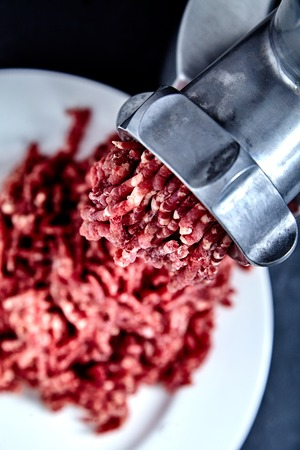 forcemeat: Close up of front part of meat grinder or mincing-machine with mincemeat in. Showing the forcemeat process. Stock Photo