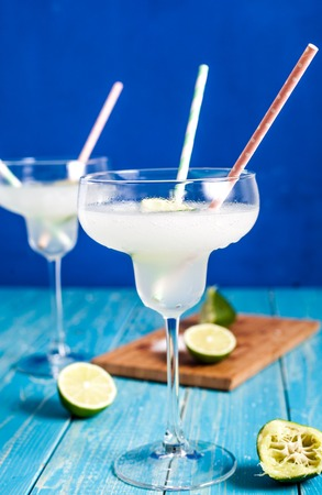 Two glasses of frozen margarita: cocktail consisting of tequila mixed with orange-flavoured liqueur, lime juice blended with ice in blender. Served with salt on the glass rim on blue background.