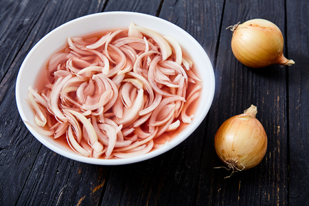 Cutted into shreds onion marinated in wine vinegar in white bowl. Pickled specific dish on wooden background. Traditional home cold appetizer. Sour, spicy taste of pickled onion goes well with fish