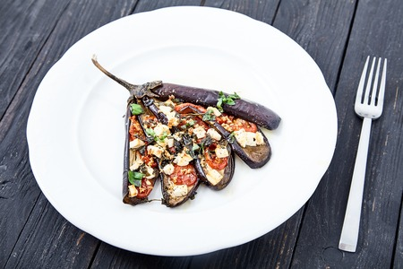 Close up shot of fan-shape baked sliced eggplant with cheese feta, cherry tomatoes, basil leaves, and olive oil on white plate. Vegetarian dish wooden background Stock Photo