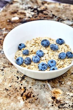 Raw oat flakes topped fresh blueberries in white bowl. Organic food on metal, grunge background. Dietary, tasty ingredients for delicious and healthy breakfast Vitamin and energy booster for whole day Stock Photo