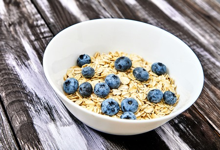 Top view shot of raw oat flakes topped fresh blueberries and in white bowl. Dietary food on dark wood back. Perfect ingredients for healthy delicious breakfast.