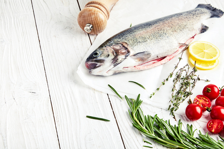 Raw fresh rainbow trout on baking paper with cherry tomatoes, slices of lemon and sprigs of rosemary and thyme. Pepper mill next to it. Preparations for cooking delicious fish. White wood background