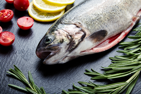 Close up shot of raw fresh rainbow trout on a black background with halved cherry tomatoes, slices of lemon and sprigs of rosemary. Preparations for cooking delicious fish. Stock Photo