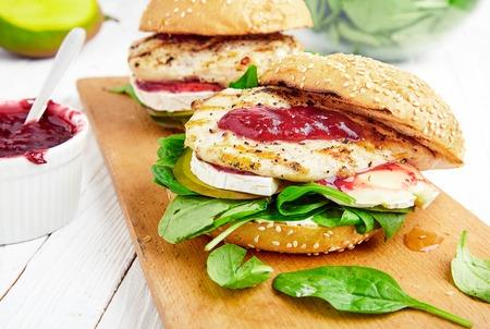 poblíž: Domácí gril kuřecí hamburger nebo sendvič s mangem, hermelínem, brusinkovou omáčkou, čerstvým špenátem a opečenou buchty. Perfektní oběd na prkénku. Mísa jam v blízkosti White, dřevo pozadí