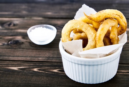 flavorful: Tasty, crunchy, golden onion rings in a white bowl with a paper. Dark wood background, a cup of salt next to it. Appetizing delicious flavorful snack from the deep fryer.