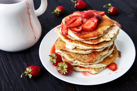 American pancakes with sliced strawberries and strawberry jam on a white plate. Delicious hot breakfast for the whole family. Black wood background, a white pitcher and fresh strawberries near it Stock Photo