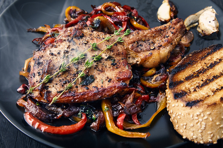 Delicious, juicy, hot club steak veal on the bone. Meat Prime rib with sauteed bell peppers and onions, decorated with two sprigs of thyme on a black plate with a toasted bun and garlic. Main dish Stock Photo