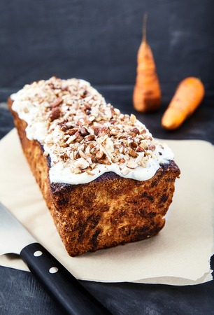 butter icing: Delicious homemade carrot cake with sweet butter cream icing and finely chopped nuts. A wonderful dessert on the baking paper with a knife nearby and two blurred carrots behind on black background.