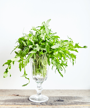 Bunch fresh arugula or rucola or rocket salad leaves at glass on wooden table. Arugula is rich in vitamins and trace elements. Perfect for salads, meat dishes, pasta or sauce pesto. Green food