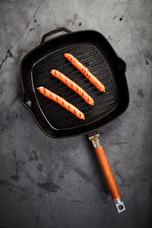 Top view of three hot Vienna sausages on the grill pan on a gray background. Ingredients for making homemade hot dogs. Perfect lunch with easy dish. Fast food snack Stock Photo