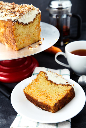 A slice of carrot cake with butter cream and crumbled nuts on a white saucer. Next to it a cup of hot tea, dessert spoon, knife and cake stand with the cake on it. Behind blurred kettle and carrots Stock Photo