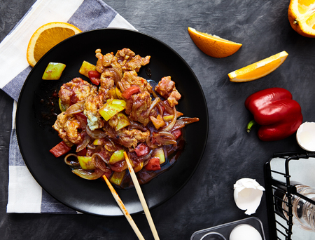 Stir fried chicken with onion, bell pepper, scrambled egg and soy sauce on a black plate with chopsticks. Asian meal on a black background, with a towel, a slice of orange and an egg shell, top view Stock Photo