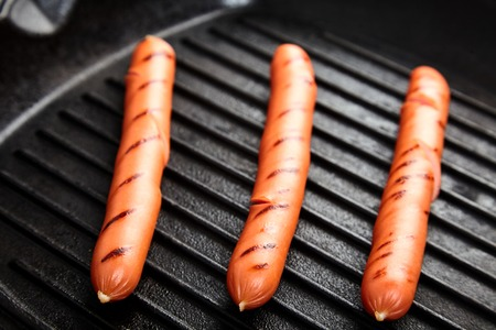 fryingpan: Close up of three hot Vienna sausages on the grill pan. Stock Photo