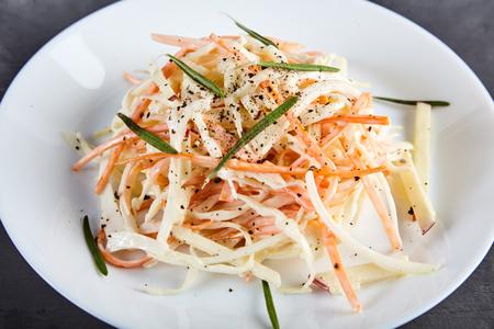mayonesa: Casera, ensalada de col crujiente ensalada hecha de la manera tradicional y decorado con hierbas y pimienta molida. zanahoria rallada, col y Apple, vestida con mayonesa en la placa blanca. Foto de archivo