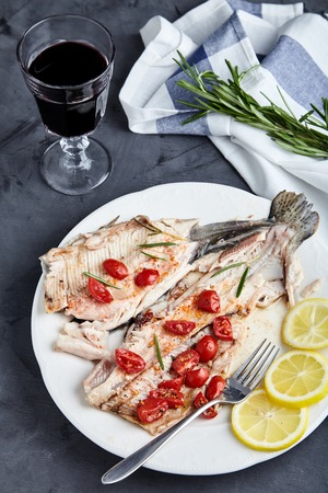 Delicious baked trout with cherry tomatoes, olive oil, lemon juice and fresh rosemary on white plate with lemon slices and fork. Behind blurred glass of red wine, rosemary and towel.