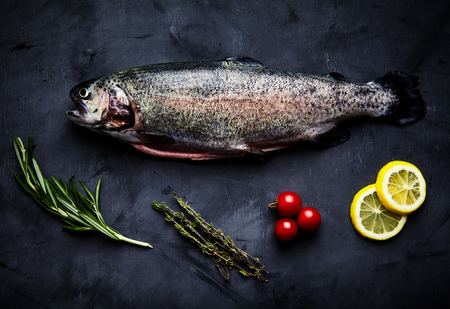 gutted: Raw fresh gutted rainbow trout with cherry tomatoes, slices of lemon, sprigs of rosemary and thyme. Preparations for cooking delicious fish on black background. Top view, saturated colors Stock Photo