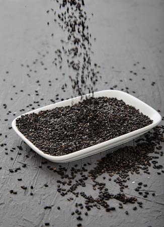 sprinkling: Black sesame sprinkling from hand in white rectangular saucer. Stock Photo