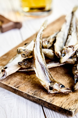Heap of dried fish on rustic chopping board, a mug of beer behind on wooden table. Dried, salted smelt delicious and popular snack to beer. Traditional Russian snack. Shallow depth of field.