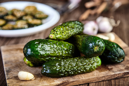 Slices of crunchy pickled cucumbers in soy sauce and rice vinegar on white plate, sprinkled with sesame seeds. Garlic, heap of pickles and cutting board behind. Chinese recipe. Shallow depth of field