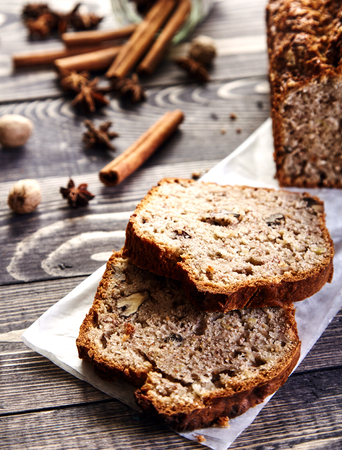 banana bread: Delicious slices of homemade banana bread with nuts. Fragrant dessert for cup of tea on wooden table. Fresh bananas, cinnamon sticks, stars of anise and walnuts in the shell next to it. Banana loaf Stock Photo