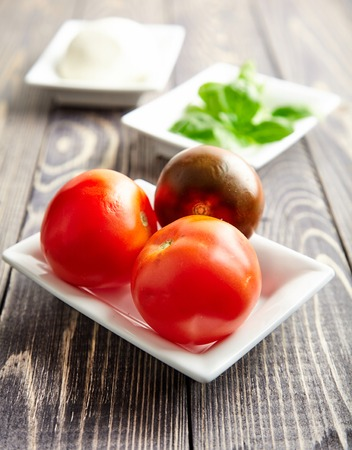 mediterranean cuisine: One of the main ingredients of Italian Caprese salad mozzarella cheese on white plate. Juicy tomatoes and fresh Basil behind. Traditional Mediterranean cuisine. Popular Italian dish on wooden table