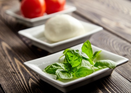 mediterranean cuisine: Main ingredients of Italian Caprese salad, mozzarella cheese, juicy tomatoes and fresh Basil in white plates. Traditional Mediterranean cuisine. Popular Italian dish on wooden table