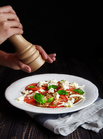mediterranean cuisine: Person seasoning Italian Caprese salad of mozzarella, ripe tomatoes and fresh Basil with black pepper from the pepper mill. Popular Italian dish on white plate. Traditional Mediterranean cuisine