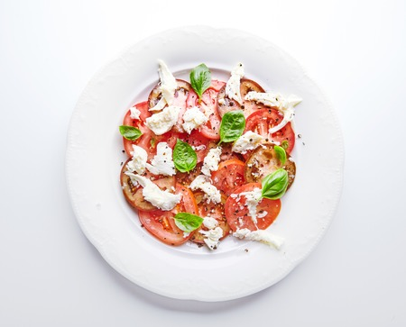 mediterranean cuisine: Traditional Italian dish Caprese salad on white plate on white background, fork near it. Basil leaves, mozzarella cheese and juicy tomatoes seasoned with black pepper and salt. Mediterranean cuisine Stock Photo