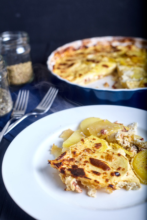 Gratin potatoes roasted with cream, eggs and cheese in white plate with ceramic blue dish on back. Dark wood background and spices in jars near it