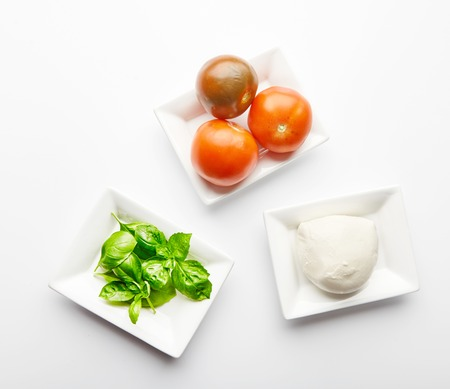 Fresh ingredients for Italian Caprese salad in white plates. Basil leaves, mozzarella cheese and juicy tomatoes. Mediterranean cuisine. Traditional Italian dish. Isolated on white background Stock Photo