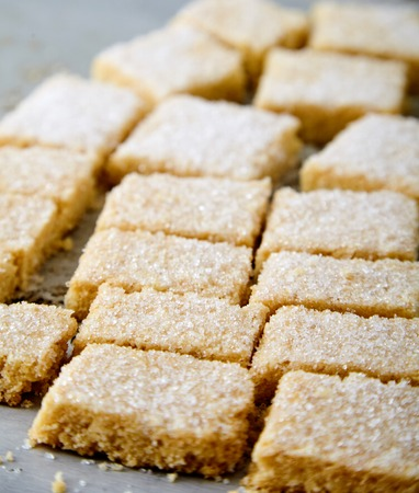 Delicious homemade sugar cookies made from semolina, butter, flour and sugar. Crumbly, delicate texture, the sugar crust on top. A little sweetness to the tea on gray background. Selective focus Stock Photo