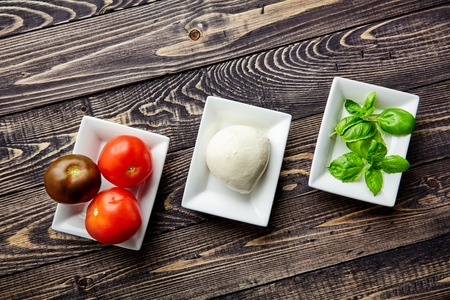 mediterranean cuisine: Top view of the main ingredients of Italian Caprese salad, mozzarella cheese, juicy tomatoes and fresh Basil in white plates. Traditional Mediterranean cuisine. Popular Italian dish on wooden table