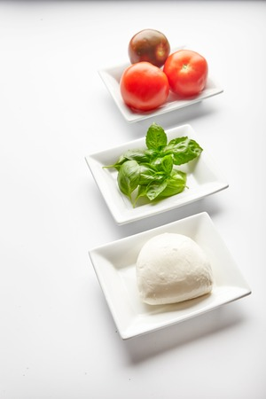 mediterranean cuisine: Fresh ingredients for Italian Caprese salad in white plates. Basil leaves, mozzarella cheese and juicy tomatoes. Mediterranean cuisine. Traditional Italian dish. Isolated on white background Stock Photo
