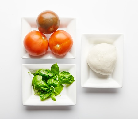 mediterranean cuisine: Fresh ingredients for Italian Caprese salad in white plates. Basil leaves, mozzarella cheese and juicy tomatoes. Mediterranean cuisine. Traditional Italian dish. on white background Stock Photo