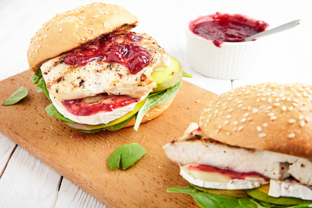 Homemade grill chicken burger or sandwich with mango, Camembert cheese, cranberry sauce, fresh spinach and toasted buns. The perfect lunch on cutting board. Bowl of jam near White, wood background