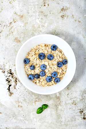 Raw oat flakes topped fresh blueberries in white bowl. Perfect ingredients for delicious and healthy breakfast. Dietary tasty food on metal, grunge backg with mint near. Top view shot with text space