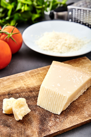 Piece of parmigiano reggiano cheese and grated parmesan cheese on wood board on stone background. Tomatoes and grater on back. Parmesan uses in pasta dishes, soups, risottos and grated over salads. Stock Photo