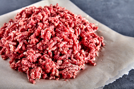 Pinky raw ground beef on a craft paper. Stone cement background Stock Photo