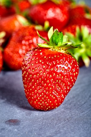 strawberies: Single fresh strawberry and bunch of many strawberies on back unfocused. Stone background.