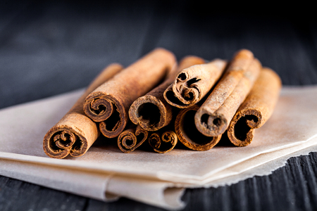 Stack of cinnamon sticks on black wood board. Dark macro photo with selective focus.