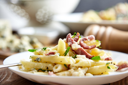 italian cuisine: Close-up shot of delicious homemade pasta of Penne rigate, celery, cooked smoked sausage, decorated with fresh herbs on white plate with fork on wooden table. Italian cuisine. Shallow depth of field Stock Photo
