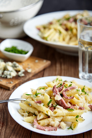 smoked sausage: Close-up shot of delicious homemade pasta of Penne rigate, celery, cooked smoked sausage, decorated with fresh herbs on white plate with fork on wooden table. Italian cuisine. Shallow depth of field Stock Photo