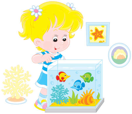 Little girl watching tropical fishes in an aquarium