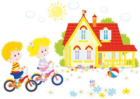 Los niños que montan las bicicletas en un día de verano cerca de una casa de campo