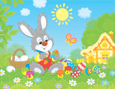 Little grey bunny painting Easter eggs on green grass among flowers on its front lawn near a small hut with thatched roof on a sunny spring day, vector illustration in a cartoon style